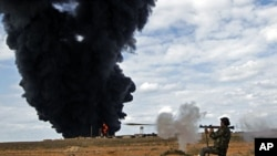 A rebel fighter fires a rocket-propelled grenade in front of a gas storage terminal during a battle on the road between Ras Lanuf and Bin Jiwad, Mar 9 2011