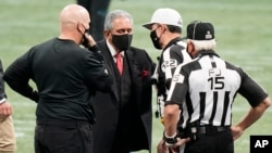 FILE - Atlanta Falcons owner Arthur Blank (C) speaks with referees before an NFL football game between the Falcons and the Panthers, Oct. 11, 2020, in Atlanta. Blank gave the University of Texas at Austin $20 million to create a new center for research into stuttering. (AP Photo)