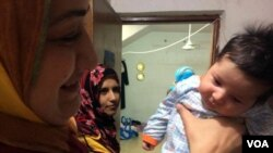 Dhoa, seen here with her baby, is torn on the issue, saying she wants both the choice to wear or not to wear a veil and the safety that comes with the military's ability to identify IS militants hiding among them in Mosul, Iraq, June 8, 2017. (H. Murdock/VOA)