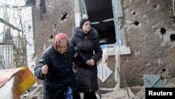 Cư dân đi bộ bên ngoài một ngôi nhà bị hư hại bởi pháo kích ở Donetsk, miền đông Ukraine, ngày 3/2/2015.