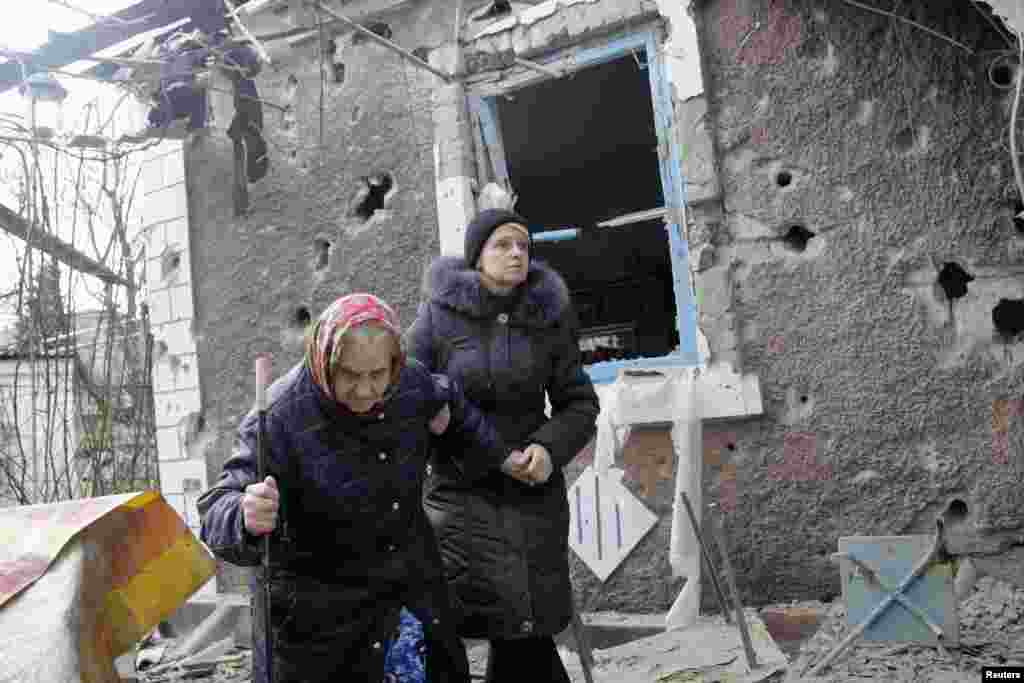 People walk outside a house, which according to locals, was recently damaged by shelling, in Donetsk, Feb. 3, 2015.