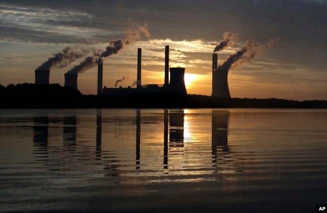 In this June, 3, 2017, file photo, the sun sets behind Georgia Power's coal-fired Plant Scherer, one of the nation's top carbon dioxide emitters, in Juliette, Ga. (AP Photo/Branden Camp, File)