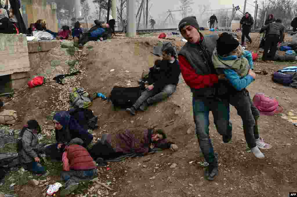 A man evacuates a boy, while other migrants and refugees lay on the ground after Macedonian police fired tear gas at hundreds of Iraqi and Syrian migrants who tried to break through the Greek border fence in Idomeni.