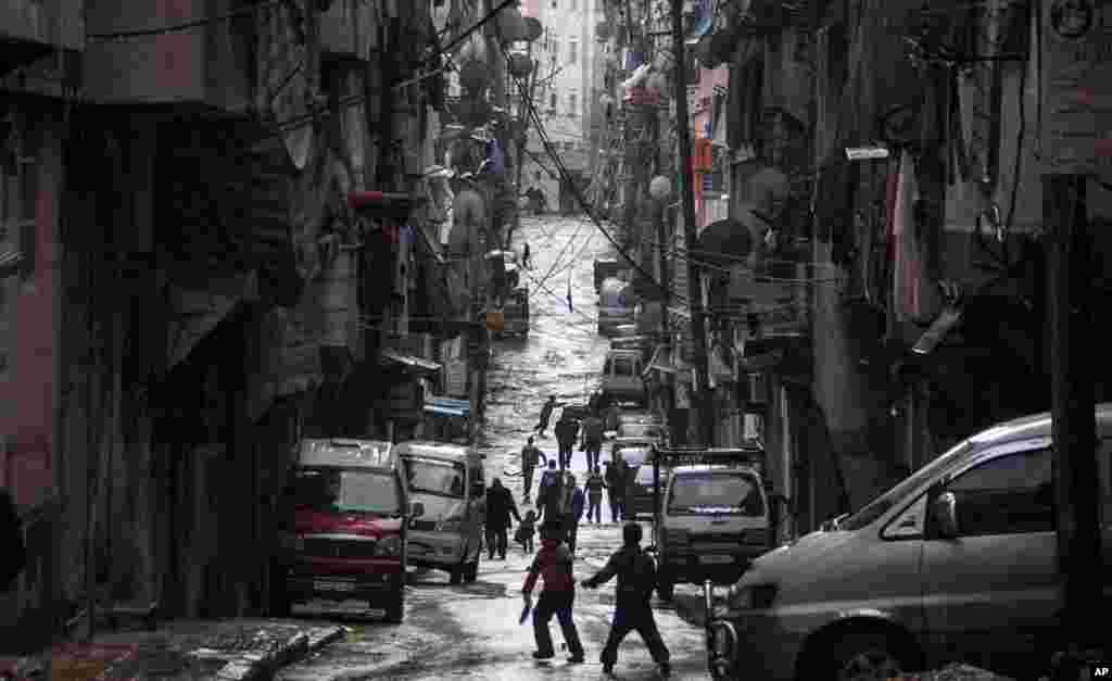 Syrians walk past damaged homes during heavy fighting between Free Syrian Army fighters and government forces in Aleppo, Syria, December 4, 2012.