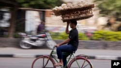 FILE - An Egyptian balances a basket of bread, in Cairo, Dec. 8, 2016.