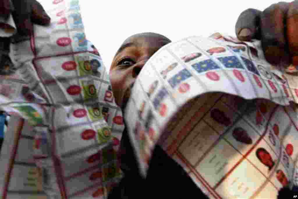 Supporters of oppositions candidate Etienne Tshisekedi parade what they claim are badly printed fraudulent photocopies of election ballots they say they found in the Bandal commune in Kinshasa, Democratic Republic of Congo, Monday Nov. 28, 2011. Polls