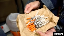 FILE - A woman shows clean syringes at a needle exchange outreach center in New York. The stigmatization of drug users in rural areas of the United States is seen as having contributed to a rise in deaths among white women.