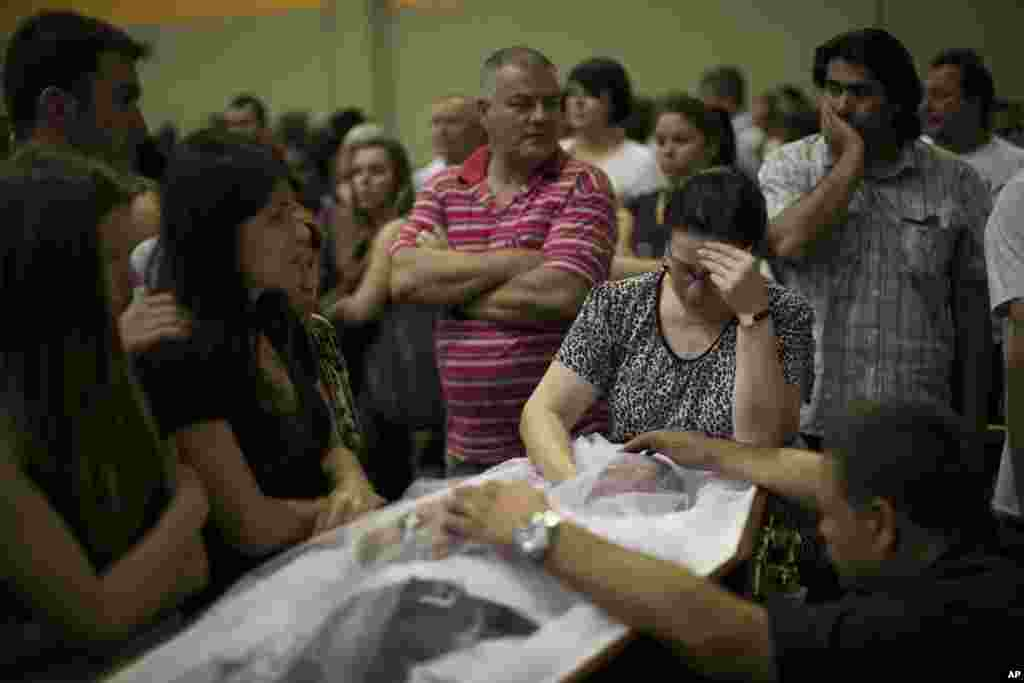 Relatives and friends mourn at the coffin containing the remains of a fire victim at a gym where bodies were brought for identification in Santa Maria city, Rio Grande do Sul state, Brazil, January 27, 2013.