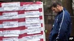 Un hombre apesadumbrado frente a una bandera cubierta con los nombres de las víctimas de Newtown.