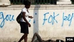 Una mujer camina al lado de un hombre tendido en el suelo, semi-inconsciente en las calles Puerto Príncipe.