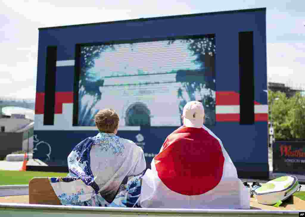 Fans watch the opening ceremony of the Tokyo 2020 Olympic Games on a big screen at the Team GB Tokyo 2020 Olympics fanzone, at Westfield, London, Friday July 23, 2021, which will be open for the next 17 days. (Dominic Lipinski/PA via AP)