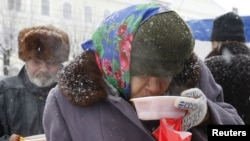 A homeless woman has a charity meal distributed by volunteers in Russia's southern city of Stavropol, December 25, 2012.