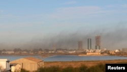 FILE - Smoke rises after an airstrike hit Maitiga airport in Tripoli, Libya, March 5, 2015. Missiles were fired Tuesday at Tripoli, including the city's only functioning airport, forcing authorities to divert flights to another airport to the south.