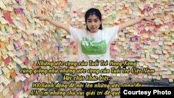 Nancy Nguyễn đứng trước tấm bảng với các mẫu nhắn gửi ủng hộ cuộc biểu tình