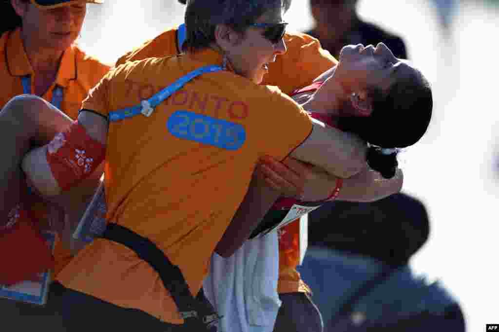 Maria Gonzalez dari Meksiko dibantu ketika jatuh setelah melewati garis akhir Lomba Jalan Cepat kategori putri Pan American Games 2015 di Toronto, Kanada. Gonzalez menang dengan waktu tempuh 1:29:24.