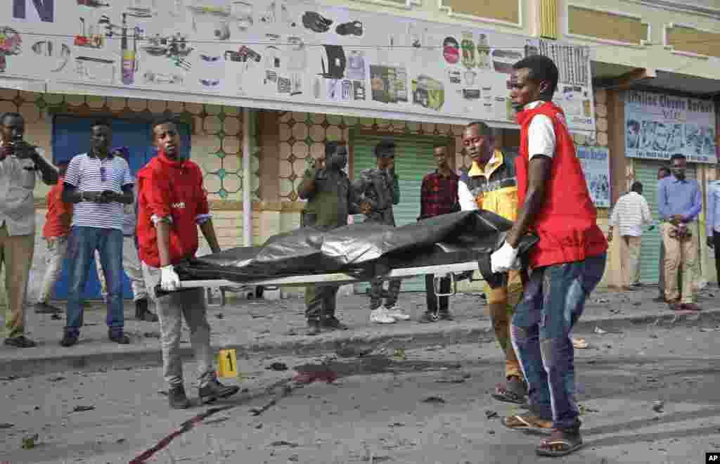 Des travailleurs médicaux enlèvent le corps d'un civil tué dans une explosion d'une voiture piégée près du Parlement, à Mogadiscio, en Somalie, le 25 mars 2018.
