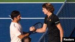Petenis Swiss Roger Federer (kanan) berjabat tangan dengan petenis Jerman Alexander Zverev. Zverev mengalahkan Federer dengan skor 6-3 and 6-4 dalam final Piala Rogers di Uniprix Stadium, Montreal