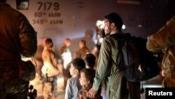 Yon papa ak pitit li ap tann pou mone abo yon avyon milite ameriken C-17 kap evakye moun soti Afghanistan, 24 Out, 2021.