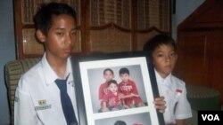 Reykhan dan Fikri Suryaman membawa foto kedua orangtua mereka, Erik Suryaman dan Neneng Nurjuwita Wati dari Cimahi, Jawa Barat, yang meninggal akibat tragedi di Mina, Arab Saudi. (VOA/R. Teja Wulan)