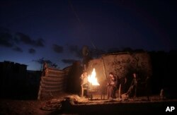 A Palestinian family warm themselves up with a fire outside their makeshift house during a power cut in a poor neighborhood in town of Khan Younis in the southern Gaza Strip, Jan. 15, 2017.