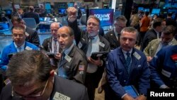 FILE - Traders gather at the post where Alibaba Group Holding Ltd is traded on the floor of the New York Stock Exchange, Sept. 22, 2014.