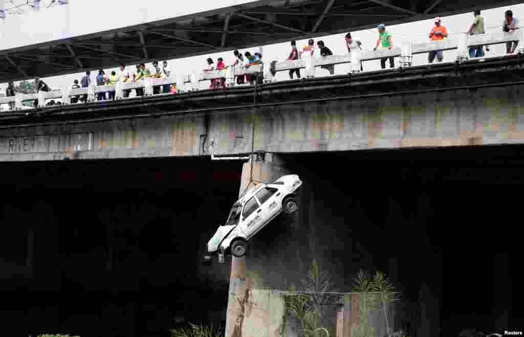 A taxi hangs beside a bridge during a metro-wide earthquake drill, along main highway EDSA in Makati, Metro Manila, the Philippines.