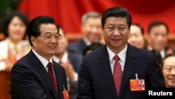 Hu Jintao (kiri) menjabat tangan Ketua Komisi Militer Pusat dan Presiden China yang baru terpilih, Xi Jinping, seusai pemungutan suara di Kongres Rakyat Nasional (NPC) di Beijing (14/3).