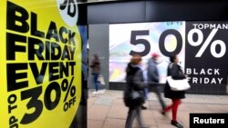 FILE - Shoppers walk past Black Friday signage on Oxford Street in London, Britain, November 23, 2018. (REUTERS/Toby Melville)