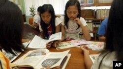 """Anak-anak membaca di salah satu perpustakaan di Jakarta Pusat (foto: dok.). LSM """"The World is Just a Book Away"""" membangun perpustakaan bagi anak-anak di Indonesia."""