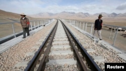 FILE - Two workers walk along the Qinghai-Tibet Railway as they check the railway track, in Dangxiong county of the Tibet Autonomous Region. (Reuters)