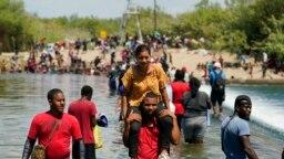 Kelompok migran asal Haiti berusaha melewati bendungan di perbatasan Amerika Serikat (AS) dan Meksiko untuk menuju AS pada 18 September 2021. Pemerintah AS tengah memulangkan kelompok migran Haiti dalam beberapa waktu terakhir. (Foto: AP/Eric Gay)