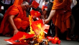 Cambodian protesters burn mock Vietnamese flags during a protest at a blocked main street in front of Vietnamese Embassy in Phnom Penh, Cambodia, Wednesday, Oct. 8, 2014.