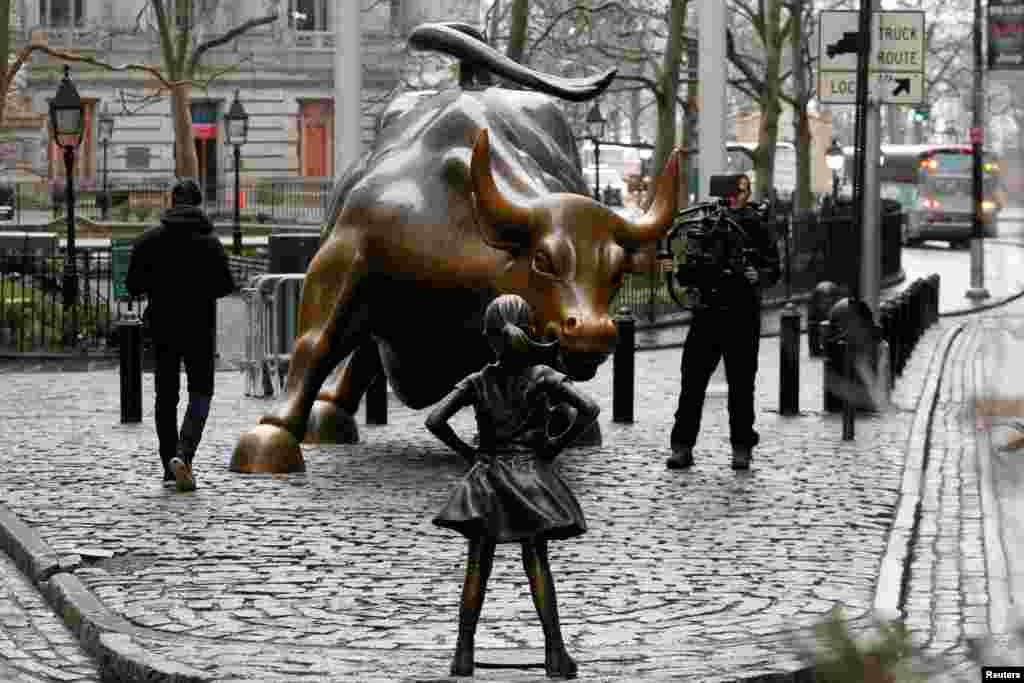 "A photographer films a statue of a girl facing a statue of the Wall Street bull in the financial district in New York, March 7, 2017. The statue was installed by investment firm State Street Global Advisors. An inscription at the base reads, ""Know the power of women in leadership. She makes a difference."""