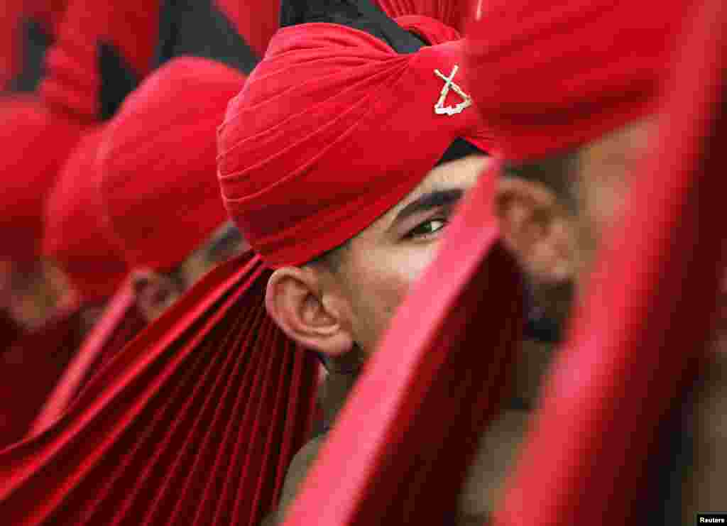 An Indian army recruit wearing his ceremonial uniform looks on as he marches during the passing out parade at a garrison in Rangreth on the outskirts of Srinagar.