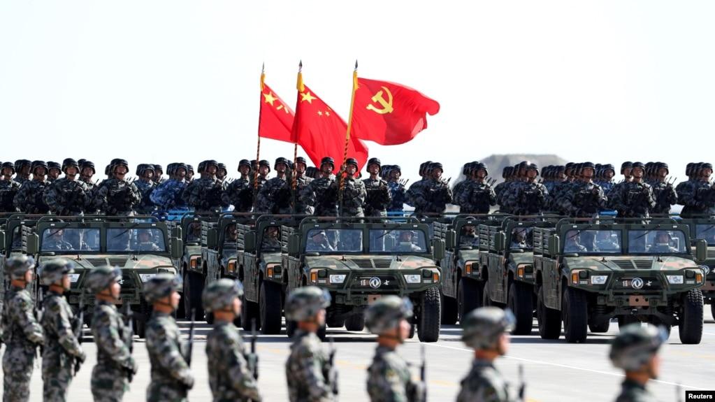 中国解放军军人在内蒙古朱日和训练基地参加阅兵,庆祝解放军建军90周年。中共党旗在前,国旗居中,军旗在后(2017年7月30日)