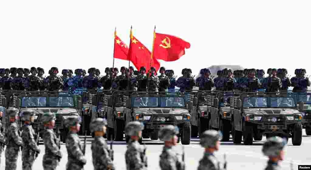 """中国解放军军人在内蒙古朱日和训练基地参加阅兵,庆祝解放军建军90周年。中共党旗在前,国旗居中,军旗在后(2017年7月30日)。这引起争议,因为中华人民共和国国旗法第十五条第二款规定:""""列队举持国旗和其他旗帜行进时,国旗应当在其他旗帜之前。"""""""