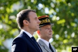 FILE - French President Emmanuel Macron, left, and Chief of the Defense Staff Gen. Pierre de Villiers, right, drive down the Champs Elysees avenue during Bastille Day parade in Paris, July 14, 2017.