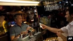 Seorang pria tengah membayar minumannya di sebuah bar di Madrid, Spanyol (Foto: dok). Ekonomi Spanyol berangsur membaik dan berhasil pulih dari resesi menjelang akhir tahun 2013.