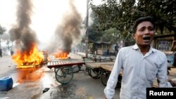 A man cries after Bangladesh's Jamaat-e-Islami party activists torched his vehicle during a clash with police in Dhaka December 13, 2013.