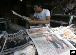 Penjaja koran membaca koran sambil menunggu pelanggan di Jakarta, 10 November 2010. (Foto: AP)