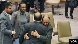 Wakil Dubes Libya di PBB Ibrahim Dabbashi (kanan) memeluk Dubes Libya di PBB, Mohamed Shalgham setelah pertemuan dengan DK PBB di New York, Jumat (25/2).