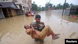 Umunyagihugu muri reta ya Tripura ateruye umutamakazi amuhungisha amukura mu kibanza catewe n'imyuzure y'imvura mu micungararo ya Agartala, mu Buhindi, itariki 14/07/2019.