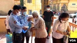 Cambodian authorities perform a temperature check on an elderly woman before entering the pagoda to celebrate Khmer New Year, Phnom Penh, Cambodia, April 14, 2020. (Hean Socheata/VOA Khmer)