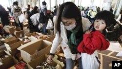 日本地震災民在庇護所內領取食物