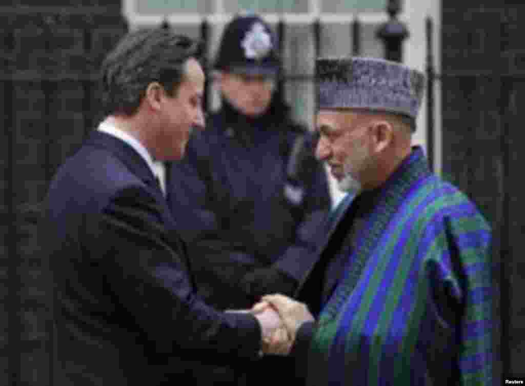 Prime Minister David Cameron (L) greets Afghanistan's President Hamid Karzai outside Downing Street ,in central London March 1, 2011. REUTERS/Toby Melville