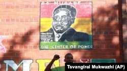 FILE: A supporter of Zimbabwean President Robert Mugabe chants the partys slogan while standing underndeath a portrait of Mugabe in Harare, Sunday, Feb. 21, 2016. (AP Photo/Tsvangirayi Mukwazhi)