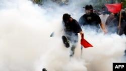 Demonstrant šutira kanister sa suzavcem koji je ispalila grčka policija tokom demonstracija ispred zgrade parlamenta, u Atini