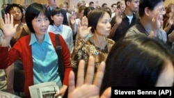 In this file photo, Mei Yu, left, and Kathy Mei, front right, both originally from China, take the oath of American citizenship in Boston, June 16, 2004.
