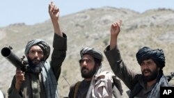 FILE - Taliban fighters react to a speech by their senior leader in the Shindand district of Herat province, Afghanistan, May 27, 2016. The rise of IS in Afghanistan has become such a priority that U.S. and Afghan forces sometimes support the Taliban while battling IS.