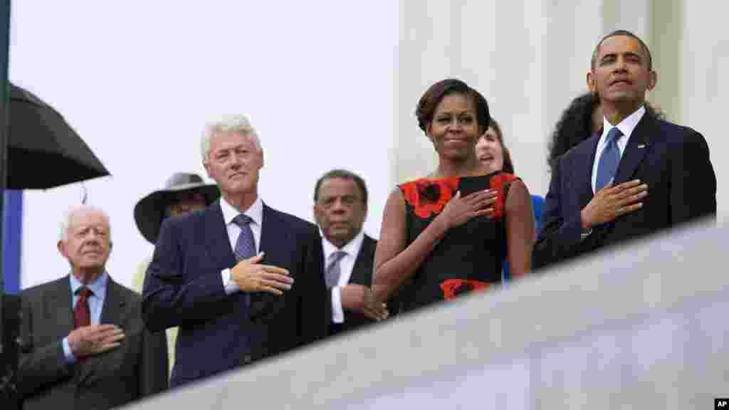 From left, former President Jimmy Carter, former President Bill Clinton, former U.N. Ambassador Andrew Young, first lady Michelle Obama, and President Barack Obama stand for the national anthem during a ceremony commemorating the 50th anniversary of the March on Washington, Aug. 28,2013.